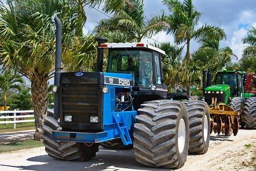 wielki niebieski traktor stoi na drodze pelnej ziekonych palm